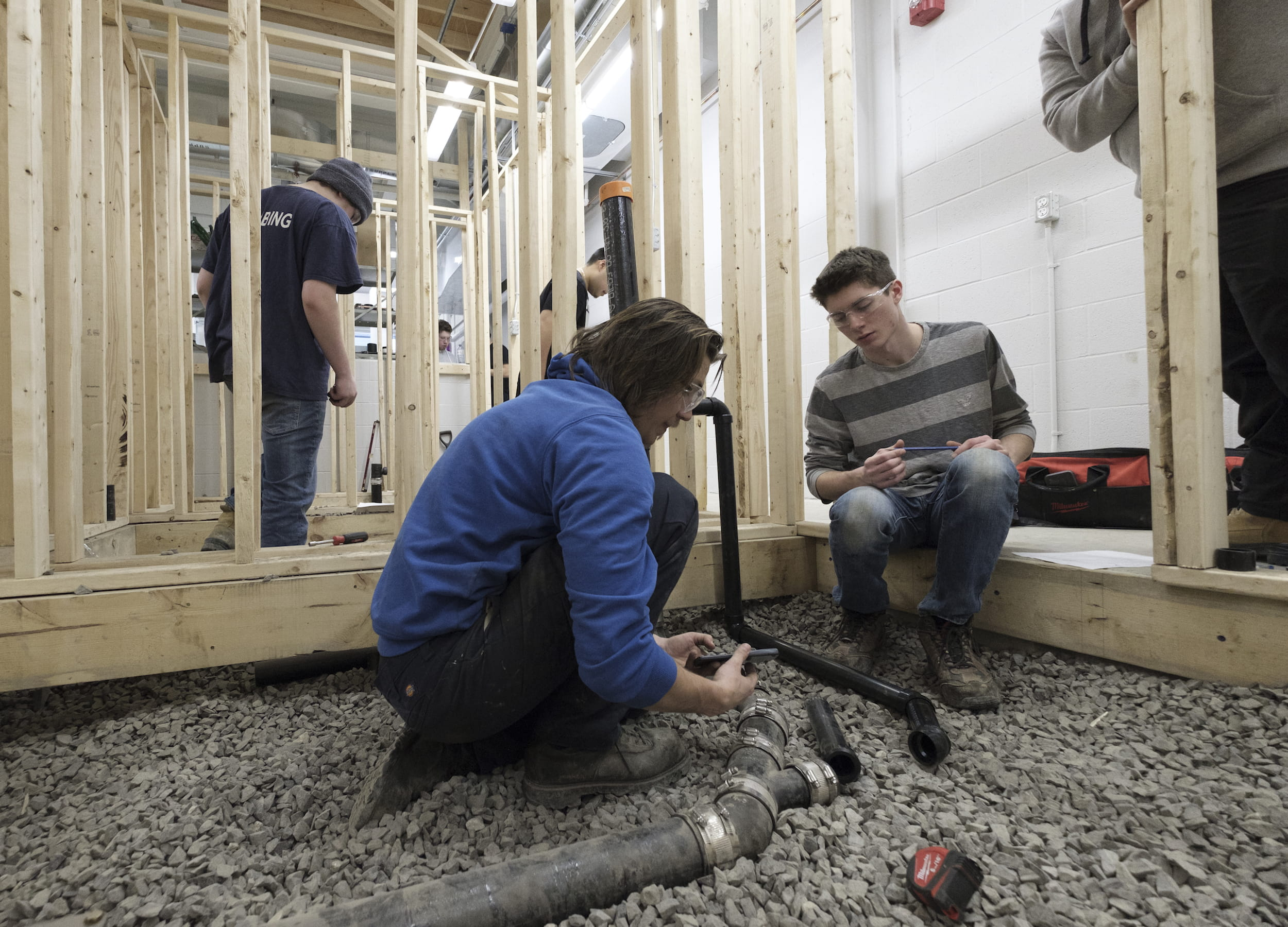 Two students crouch over a series of pipes in wooden house framing